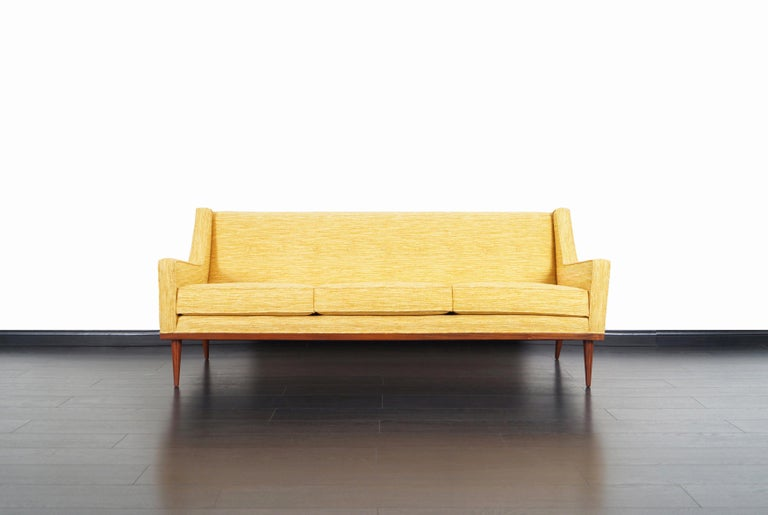 Fabulous mid-century sofa designed by Milo Baughman for James Inc. in the United States, circa 1950s. This sofa has been professionally reupholstered by our expert craftsmen. Features a clean design with sleek angled armrests. The sofa sits on a
