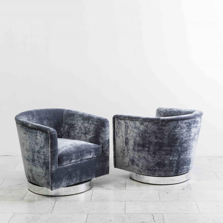 A beautiful pair of swivel chairs designed by Milo Baughman. Each chair has a circular chrome base that swivels with ease. Elegant in design, the chairs are also extremely comfortable, offering wonderful back support. The chairs feature new