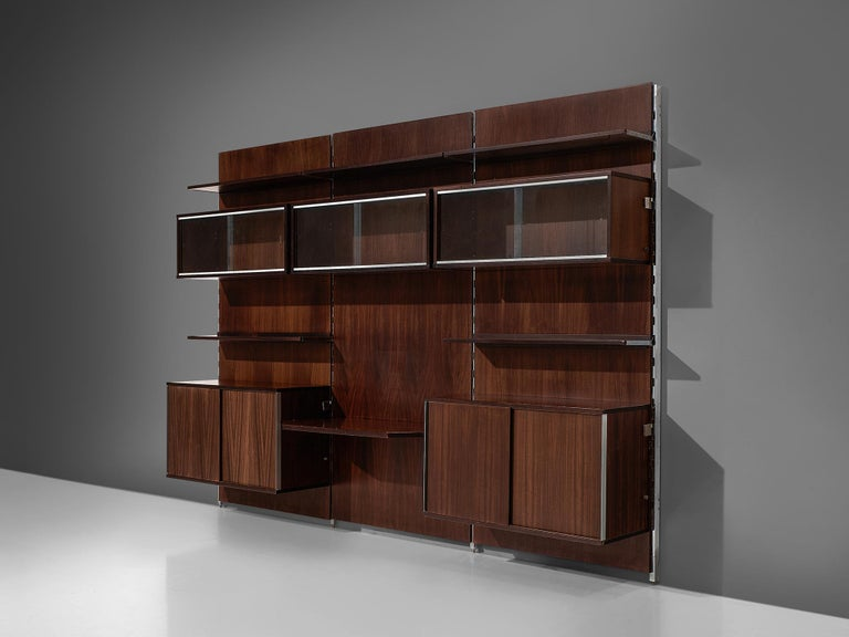 MIM Roma, cabinet, rosewood and metal, Italy, 1960s.  The monumental wall-mounted cabinet consists of four wall panels with various different storage facilities. The finish and details of this shelving wall unit are of a high standard. The piece