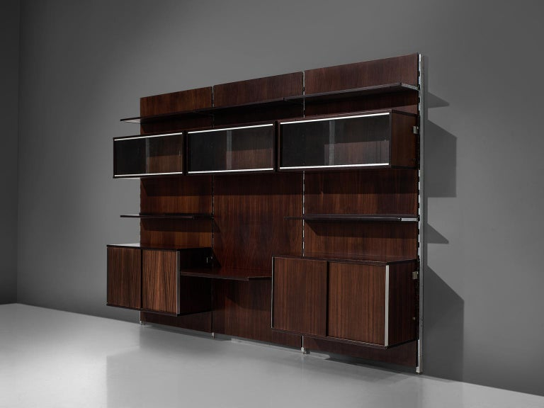 MIM Roma, cabinet, rosewood and metal, Italy, 1960s.  The monumental wall-mounted cabinet consists of three wall panels with various storage facilities. The finish and details of this shelving wall unit are of a high standard. The piece would cover