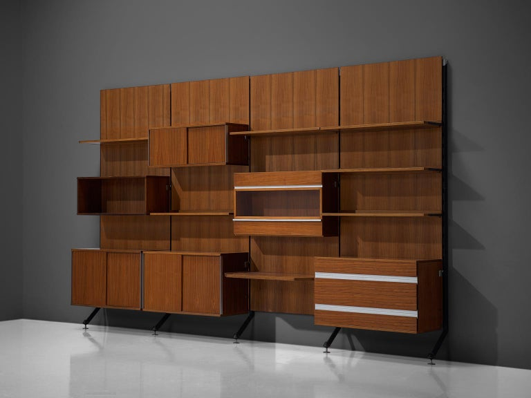 MIM Roma, cabinet, teak and aluminium, Italy, 1960s.  The monumental wall-mounted cabinet consists of four wall panels with various different storage facilities such as shelves, drawers and cabinet. The finish and details of this shelving wall