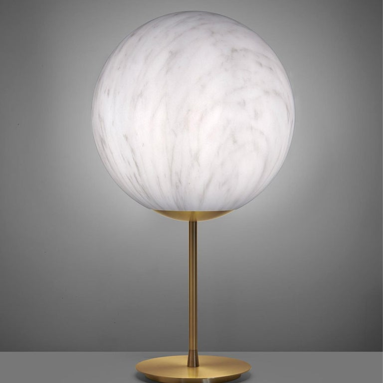 The spherical shape of mineral stand lights up every kind of indoor settings with essentiality and elegance. The particular Carrara marble finishing, with red or grey veins, makes the lamp refine and timeless. The brass stem makes both the table and