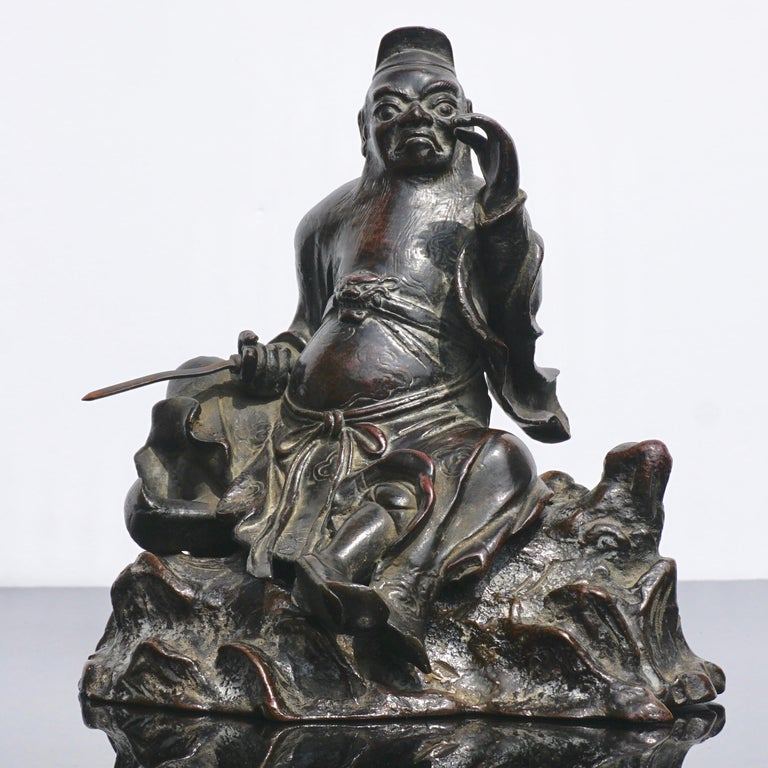A Chinese Ming dynasty two-piece bronze incense censer or cache in the Form of Guandi or Guan Yu holding a sword in his right hand sitting on a natural boulder. The sculpture or figure with a hat, long beard is elegantly robed with a lion or tiger