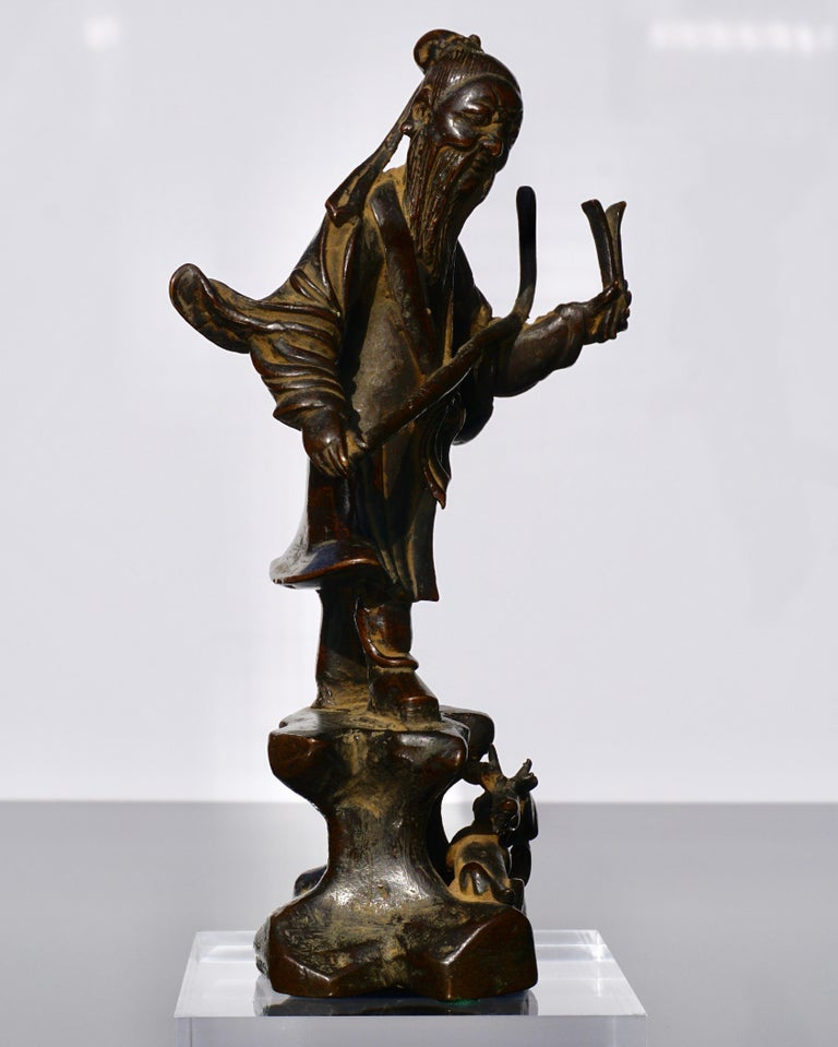 A very whimsical and spirited Luohan from calls in the beasts of the forest as to protect them from harm. These bronzes are rare but come up for sale from time to time. This piece shows the signs of Ming art; flowing robes, mystical beast like