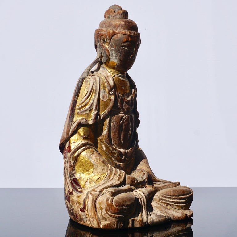 A beautifully carved wooden Buddhist spiritual figure with traces of gold gilded leaf. The seated Buddha statue is gazing down with hand clasped in his lap. Traces old ox blood polychrome on robe verso. Compartment for parlayed cutout on back seams