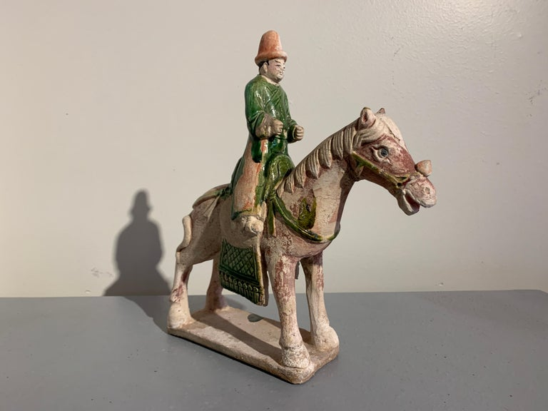 A charming Chinese Ming Dynasty figural group of a horse and rider with an associated attendant, green glazed pottery, Ming Dynasty (1368 to 1644), circa 16th century, China.   The group comprised of a horse with a mounted rider, and a separate
