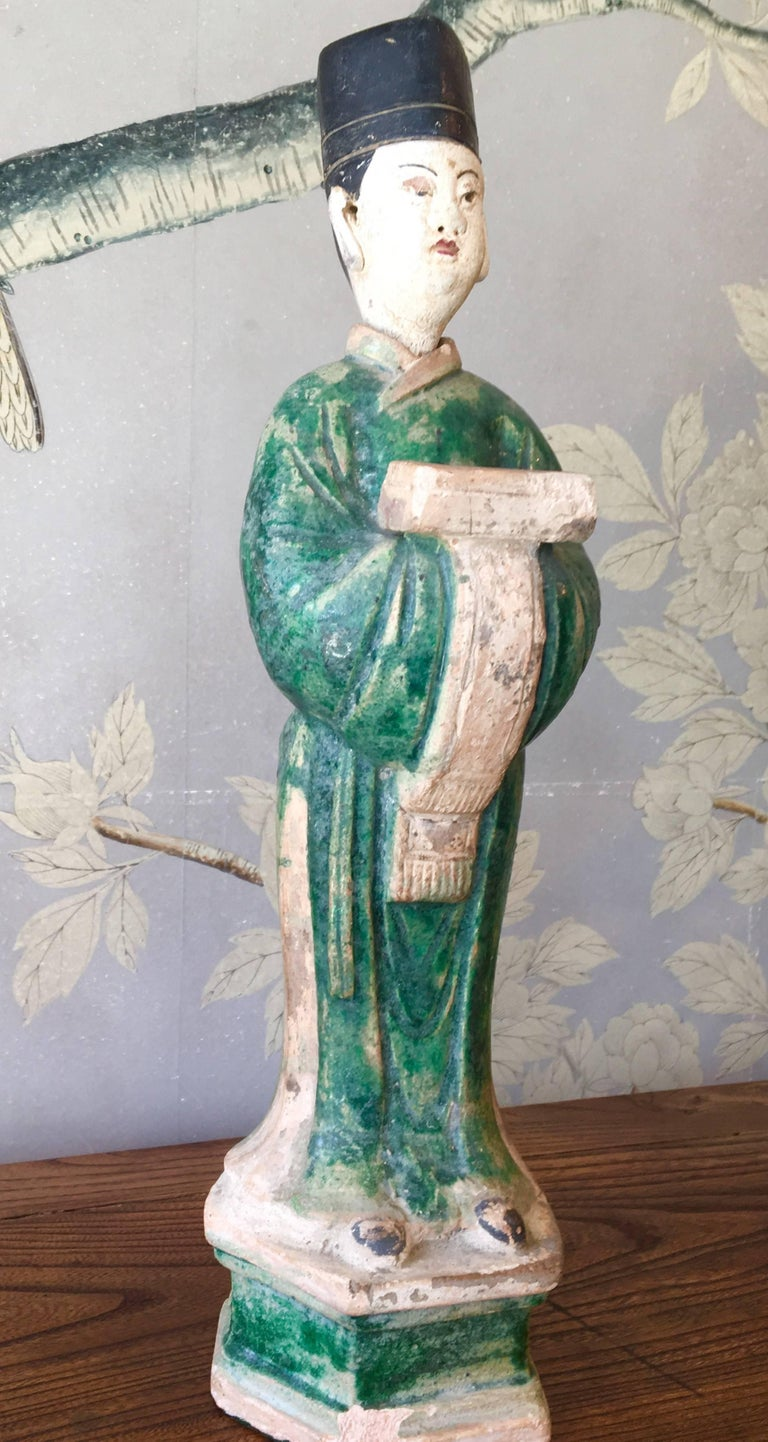 A Ming style Chinese pottery figure of an attendant, partially glazed on an attached hexagonal base.