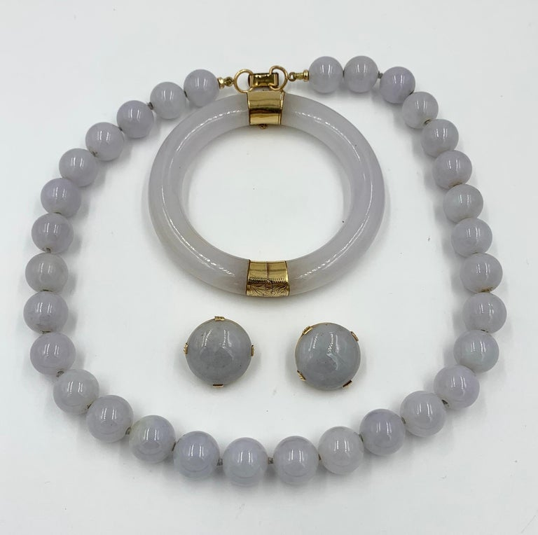 A spectacular and rare Ming's Lavender Jade Suite.   The suite comprising a necklace, earrings and bangle bracelet.  The highly coveted Ming's jade jewelry of Hawaii is becoming exceedingly difficult to find.   And here we have a suite.  Bangle