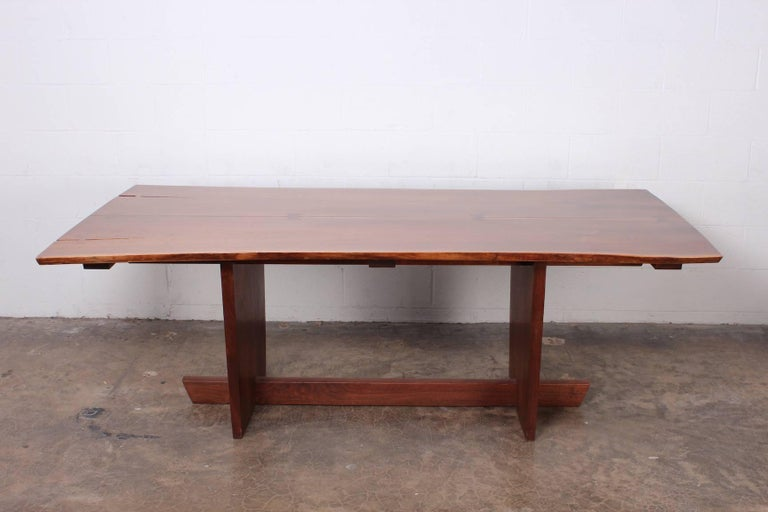 A walnut, Minguren II dining table with rosewood bowties by Mira Nakashima, 2005.