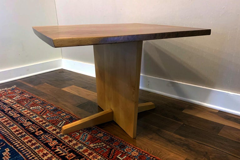 A square pedestal table with Minguren I type support by George Nakashima circa 1968. Featuring an English walnut top with holly base, two free contoured edges and prominent wood grains. The table can be used as a coffee or side table but also makes