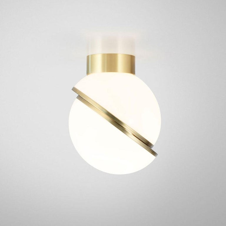 A miniature version of the popular crescent light, this illuminated sphere is sliced asymmetrically in half to reveal a crescent-shaped brushed brass fascia. Mini Crescent seamlessly combines the solid and the opaque.