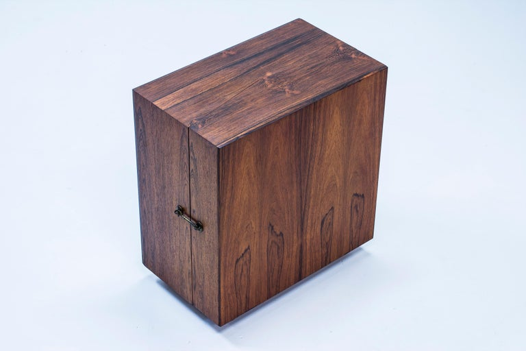 Mini dry bar cabinet designed by Henry Rosengren Hansen. Produced in Denmark by Brande Møbelfabrik during the 1960s. Made from rosewood on the outside with black lacquered oak on the inside with small brass details. Rolling on wheels. Very good