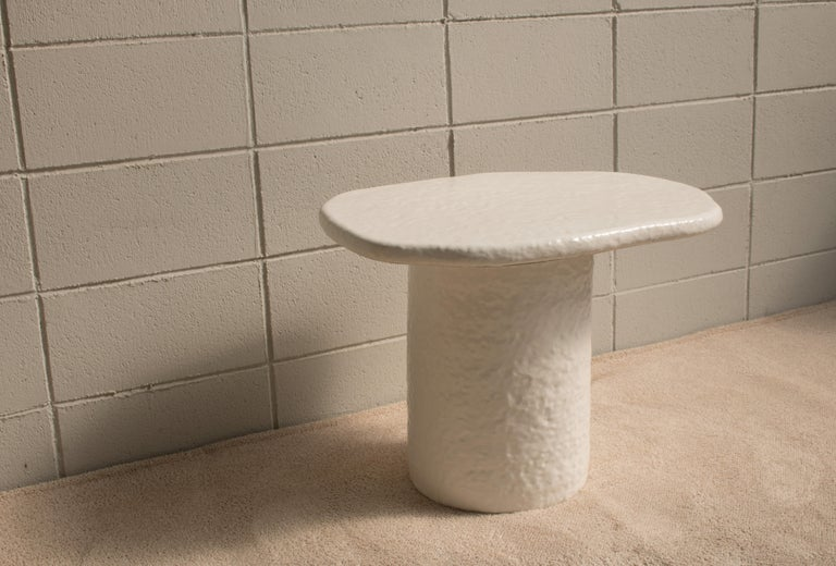 A side table with a top plate over a cylinder. The lower part with the cylinder shape and upper part were made separately and used epoxy materials after going through the firing process. The bottom of the top plate is finished with epoxy, so the