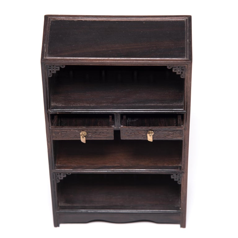 A full size bookcase with this level of workmanship and detail would be an incredible find, but this beautiful piece of furniture—at only nine inches tall—is perfectly constructed down to the tiniest minutia. The bookcase was made in northern China
