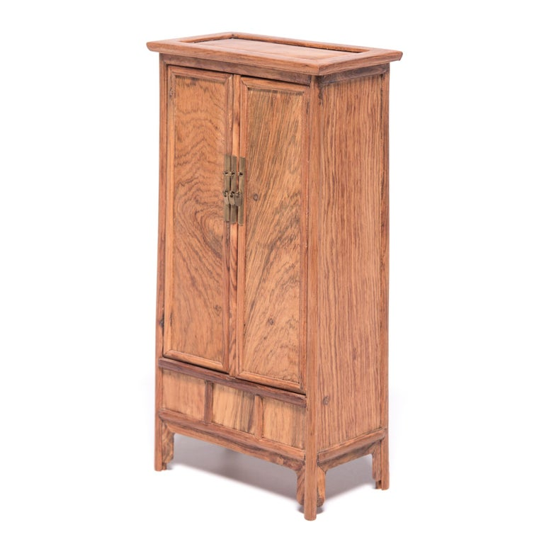 A full size cabinet with this level of workmanship would be an incredible find, but this beautiful piece of furniture, at only nine inches tall, is perfectly constructed down to the tiniest minutia. The petite cabinet was made in northern China out