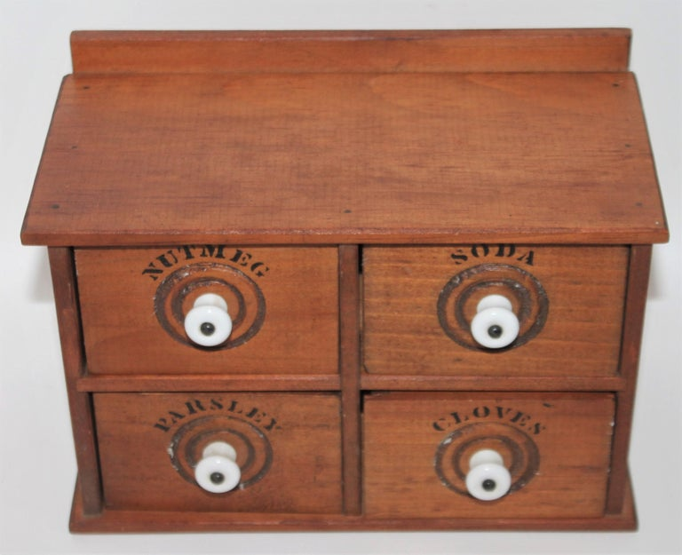Miniature early 20th century spice box with original hardware and original porcelain drawer pulls. This small table top spice box has great bones.