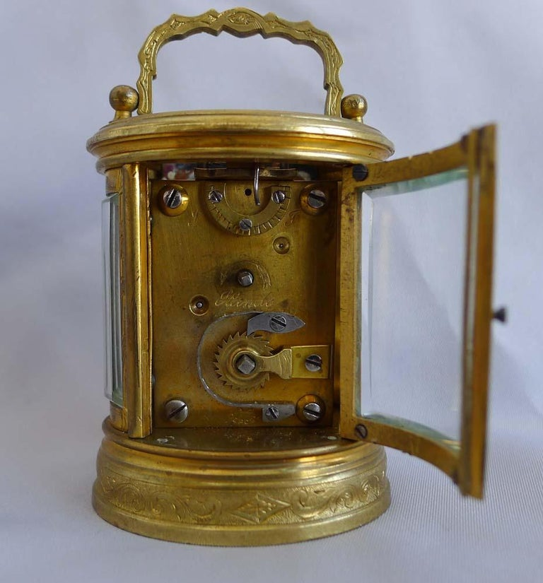 Carriage clock, oval, engraved, miniature and French. However this one was made for the English market as it is engraved on the backplate below the escapement, F and S for fast and slow rather than A and R for advance and retard as it would be for
