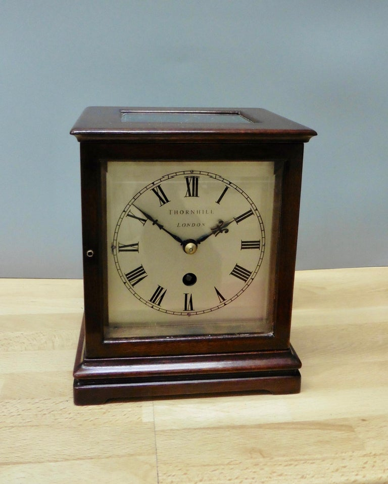 Miniature mahogany library clock, Thornhill, London  Miniature mahogany library clock standing on a stepped plinth with pad feet. Four glass panels with beveled glass and glass panel to the top to view the movement.  Silvered dial with Roman