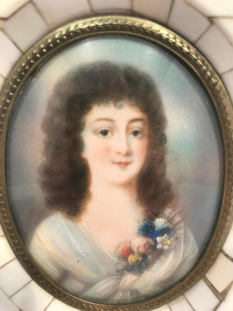 Miniature portrait of a beautiful young lady in a bone frame with a repoussé inner gilt brass filet. The portrait is hand painted on bone and retains its original crown glass.  (This item is eligible for a gift box upon request.)
