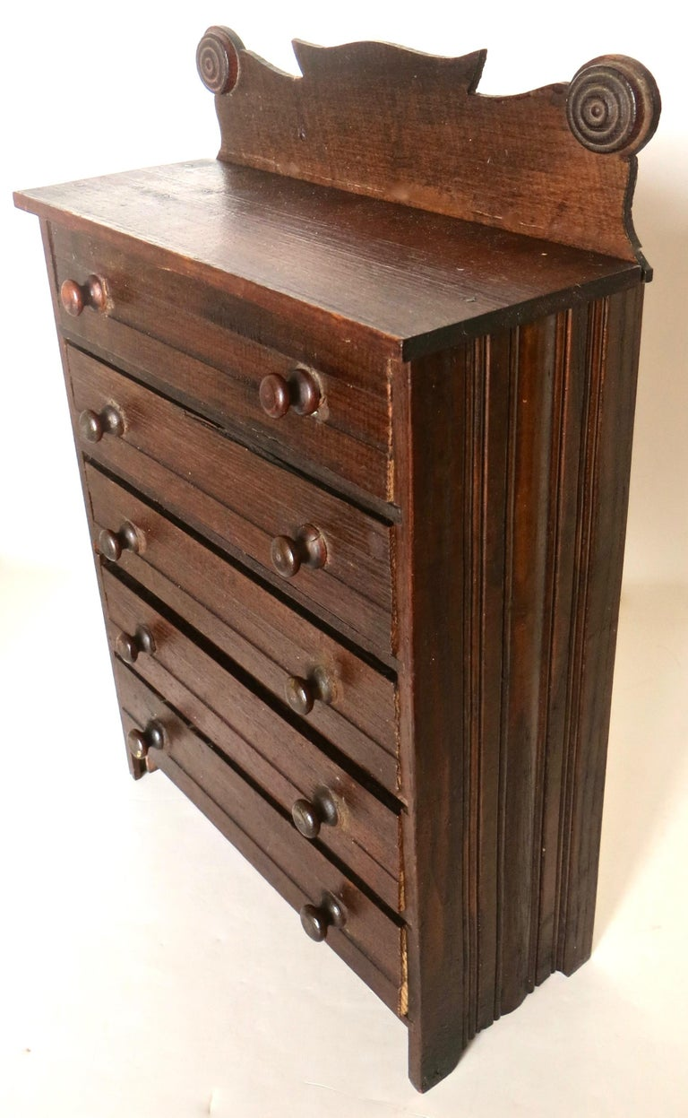 This late 19th century miniature 5-drawer dresser was likely used as a salesman sample by an itinerant sales person who traveled the countryside promoting his articles, usually by seeking out merchants to take orders based on this miniature chest,
