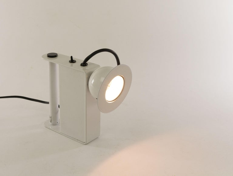 Minibox table lampdesigned byGae Aulenti & Piero Castiglioniand manufactured by Stilnovo in 1980.  This halogen table lamp can also be used as a 'torch' thanks to the handy handle. However, due to the power cord, it can only be used inside the