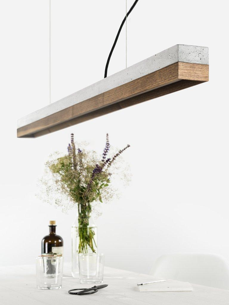 The rectangular pendant lamp [C1] is cast from a light grey concrete. It combines modern materials like nut wood and concrete to a minimal, Industrial light.  With an edge length of 122 x 8 x 8 cm, the lamp is perfect suitable over a long dining