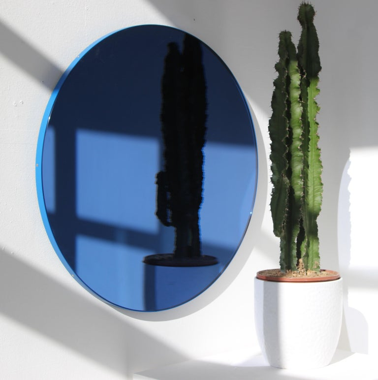 Delightful handcrafted blue tinted round mirror with a funky blue frame.  Ideal above a console table in the hallway, above a beautiful fireplace, in the bedroom or in the bathroom.  Design tip: looks stunning used as a cluster in different