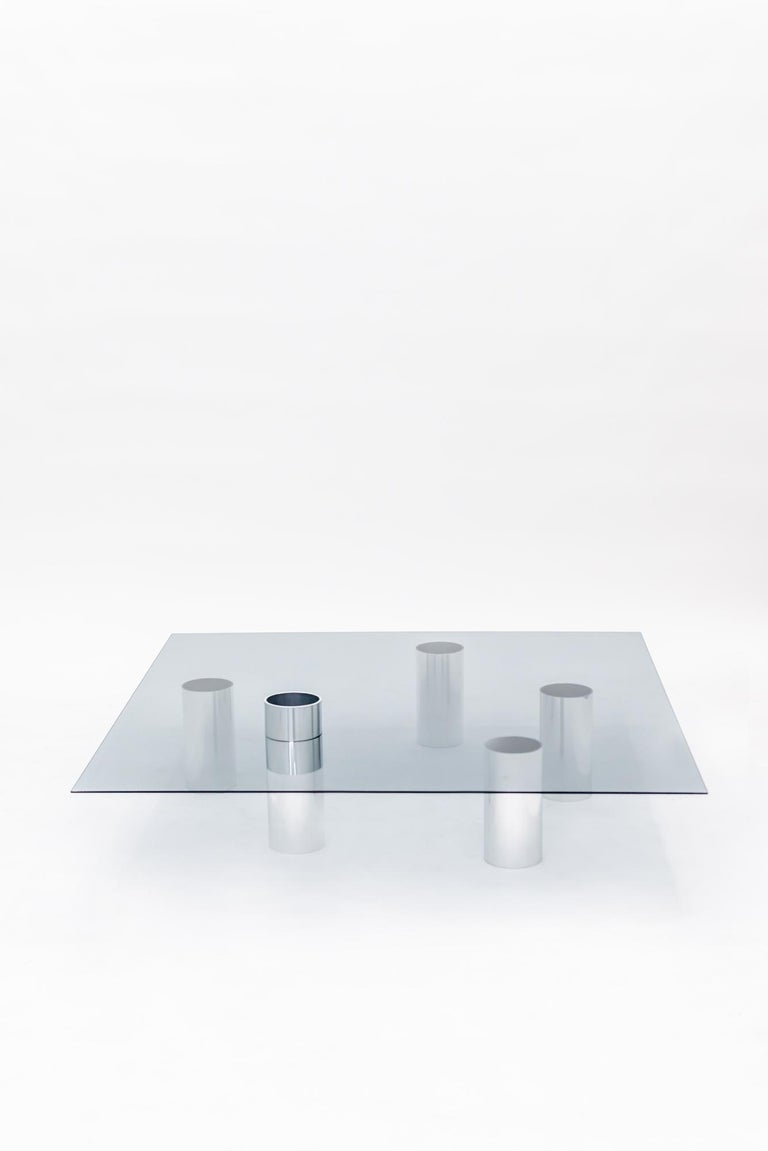 A thin, tempered smoked gray glass sits atop the set coffee table by Deon Rubi, creating an ample functional surface. The modular legs are made from 3-inch polished aluminum tubes and can be arranged as desired, as long as balance is kept. A playful