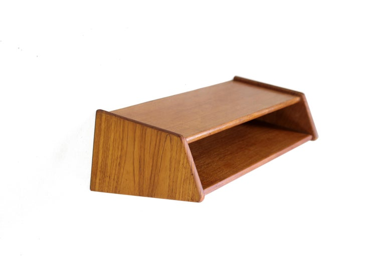 This wall shelf was designed by Kai Kristiansen and produced in Denmark by Aksel Kjersgaard. This shelf is made of solid teak and has two storage shelves, or one compartment. Use this Minimalist storage unit under a mirror in the hallway, for
