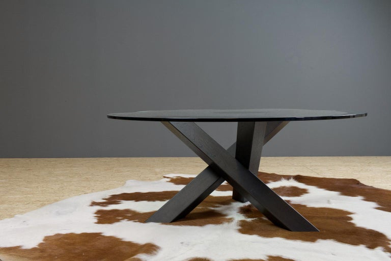 Minimalistic and a bit brutal round coffee table in dark oak, new made. The heavy and thick glass top is positioned on a solid and massive dark oak tripod. The solid wooden legs are made of massive oak and blackened/ ebonized with a high quality
