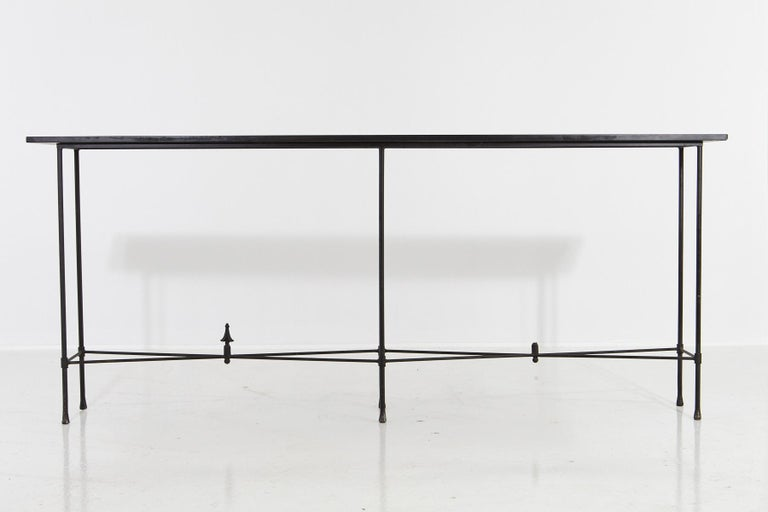 Minimalistic custom made, 7 ft. long wrought iron console with slate top, circa 1980s. The console has a very, minimalistic, elegant appearance through its thin metal construction and the narrow long piece of slate. One of the finials is missing