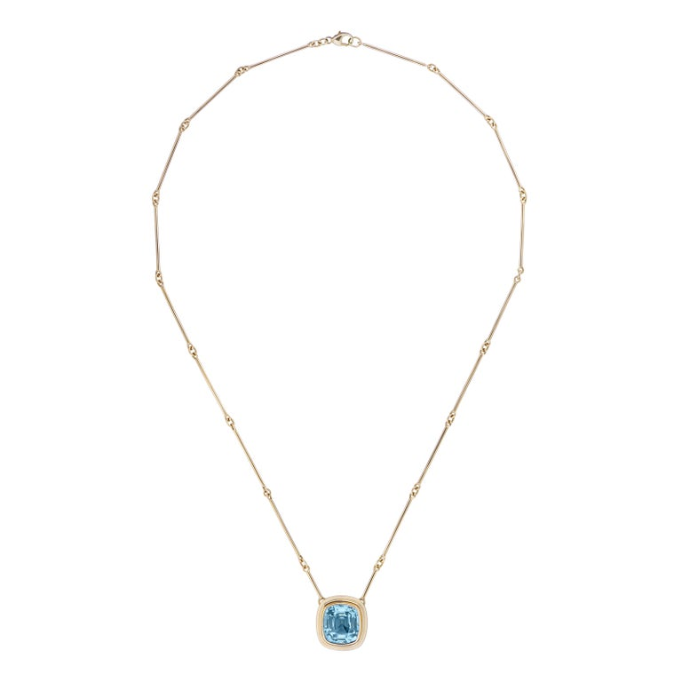 A top quality 6.97ct cushion cut Aquamarine set in 18kt yellow gold on a gold bar chain 18 inches.  This statement necklace is so striking and sets off any outfit. The colour of the Aquamarine is so beautiful a true blue that really pops. The latest