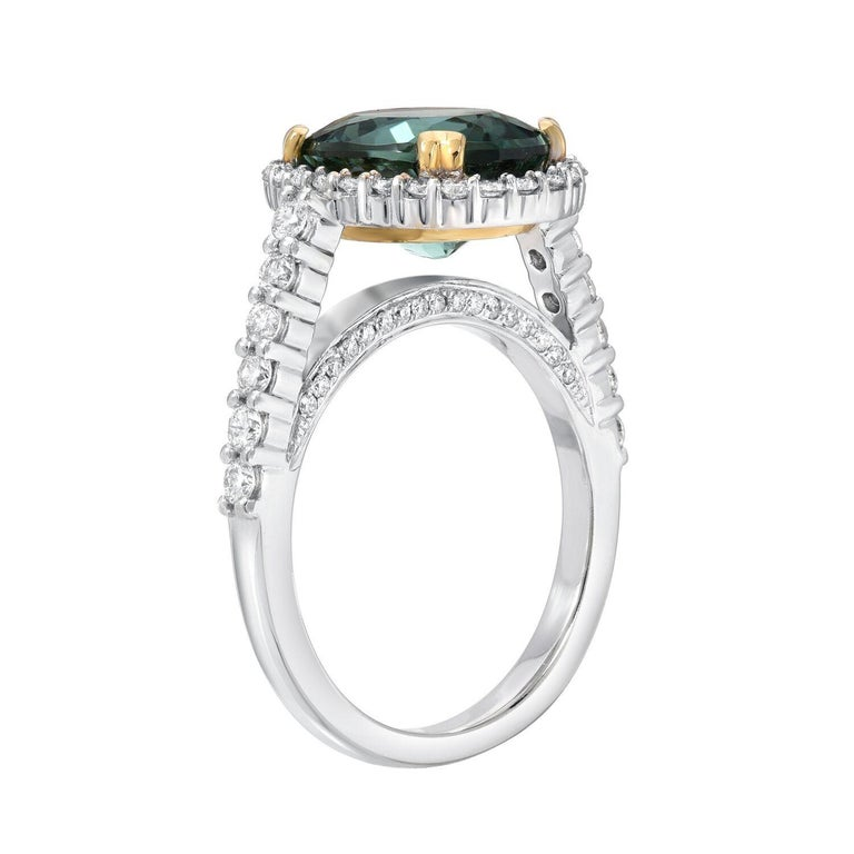 Spectacular oval Mint Green Tourmaline, weighing a total of 4.48 carats, is adorned by a total 0.88 carats of round brilliant diamonds, in this 18K yellow and white gold engagement ring or cocktail ring. Ring size 7. Re-sizing is complimentary upon