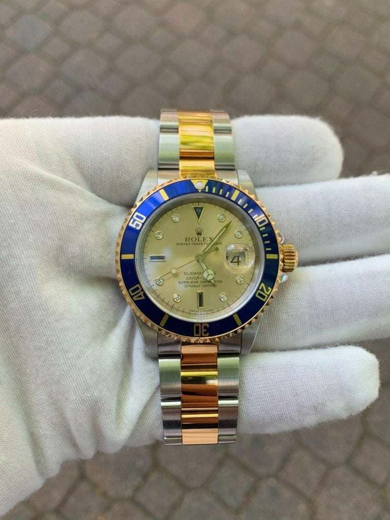 This amazingly and super well-kept Rolex Submariner comes with its original box and papers and remains in excellent physical and mechanical condition. The dial is adorned with genuine round single cut diamonds and custom cut sapphires. The rotating