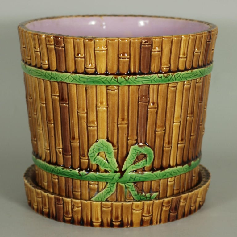 Minton Majolica planter and stand which features bamboo cane-effect sides, bound together with green ribbon. Brown ground version. Coloration: brown, green, pink, are predominant. The piece bears maker's marks for the Minton pottery. Marks include a