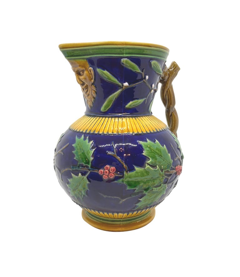 Minton Majolica large Christmas wine ewer, the body of the jug with relief molded holly branches encircling, with mistletoe, on a cobalt blue ground, the spout with a Bacchus mask, the handle formed as entwined twigs, impressed marks to reverse: