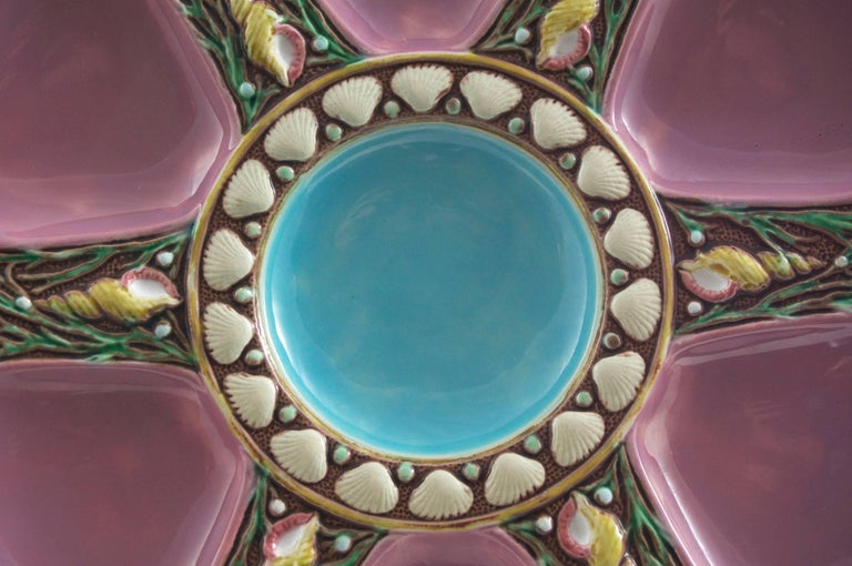 Minton Majolica oyster plate in pink; Six spokes and central well; Shell and seaweed ornamentation on each spoke; Impressed Minton; four available shape number 1323 with Minton date marks for 1873, 1874, and 1875. For over 28 years we have been