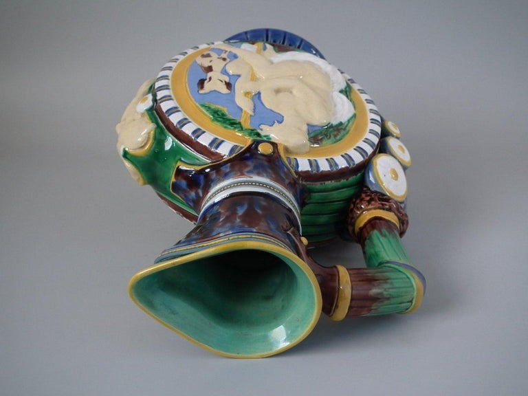 Minton Majolica jug or pitcher which features circular panels to the sides, depicting classical figures with dogs. (Diana, the huntress on one side.) Grotesque mask to the front. Coloration: Green, blue, ochre, are predominant.