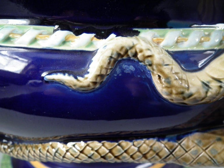 Minton Majolica jardinière which features two snakes with their tails entwined forming the handles. Cobalt blue ground version. Coloration: Pink, ochre, cobalt blue, are predominant. The piece bears maker's marks for the Minton pottery. Bears a