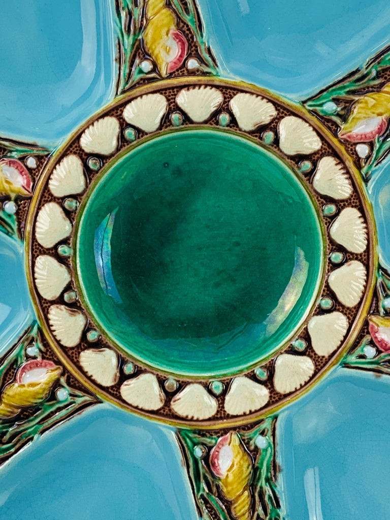 Minton Majolica six well oyster plate, the wells glazed in turquoise blue, each well separated by shells and seaweed, the central well glazed in green, bordered with shells. Impressed marks to reverse: 'Minton' with Minton date cypher for 1873