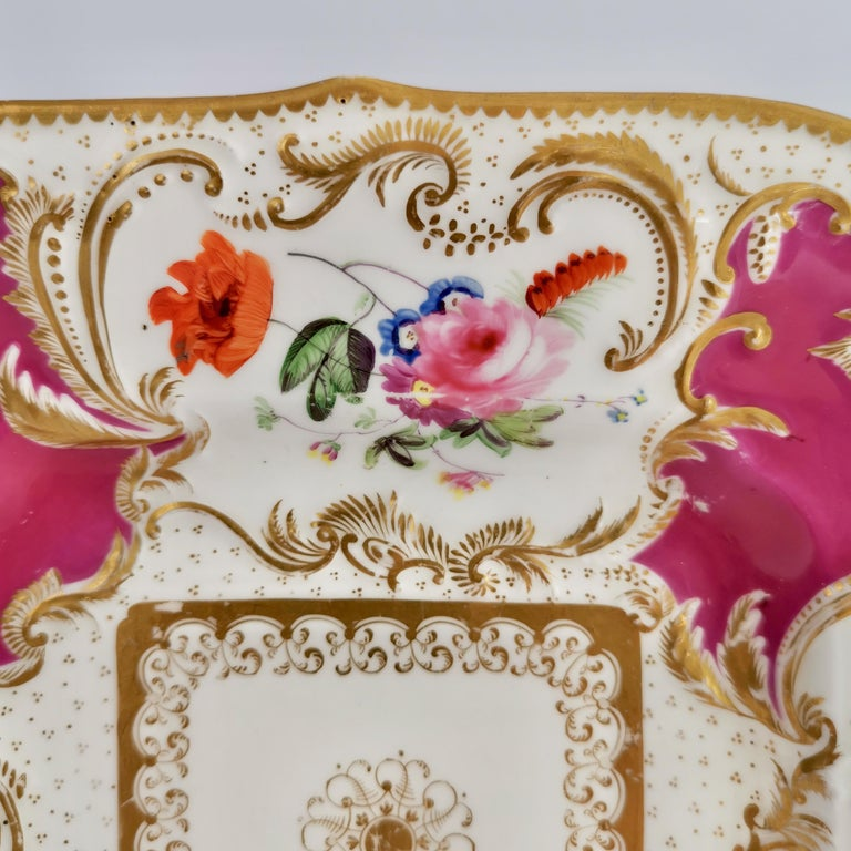 This is a rather stunning cake plate made by Minton in about 1830, which was the Rococo Revival era. This plate is decorated in a maroon ground with hand painted flower reserves and lavish gilding, and would have belonged to a large tea service.