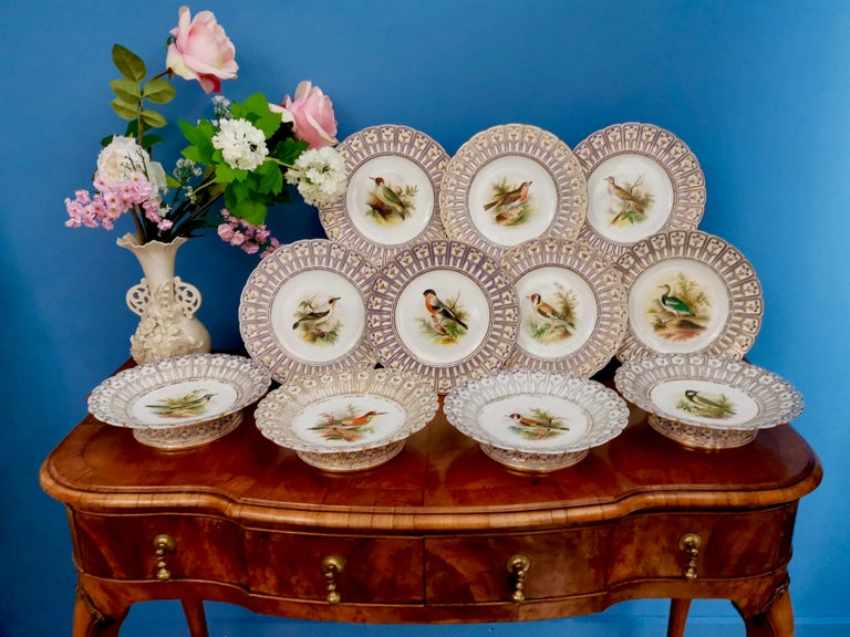 This is a stunning porcelain dessert service made by Minton in 1851, which was the Victorian era. It has hand painted named birds by the famous painter Joseph Smith, and a beautiful reticulated border called the