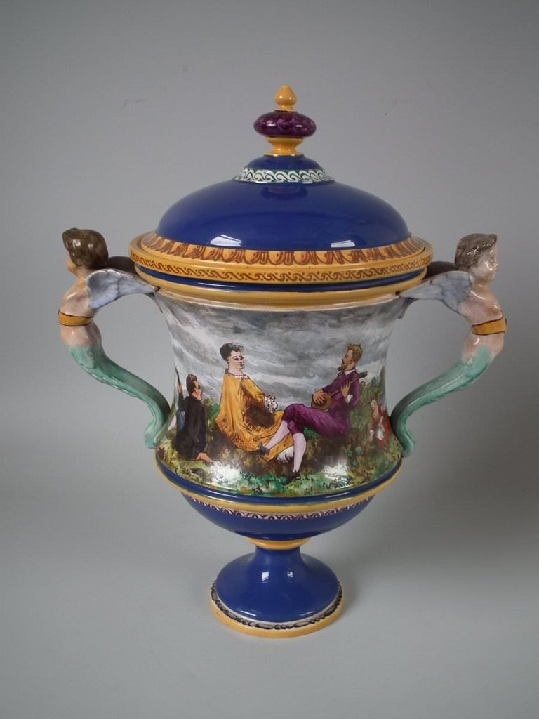 Rare Minton Tin-Glazed Majolica Pictorial lidded vase with cupid handles. Features a pictorial scene of people in a country landscape. The vase was painted by J D Rochfort - an artist who painted Minton pottery, active 1860s-1870s, who took up