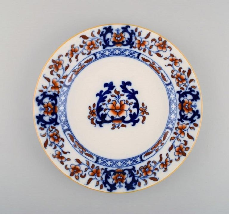 Mintons, England. Nine antique dinner plates in hand-painted faience.  Chinese style, early 20th century. Diameter: 25.5 cm. In excellent condition. Stamped.