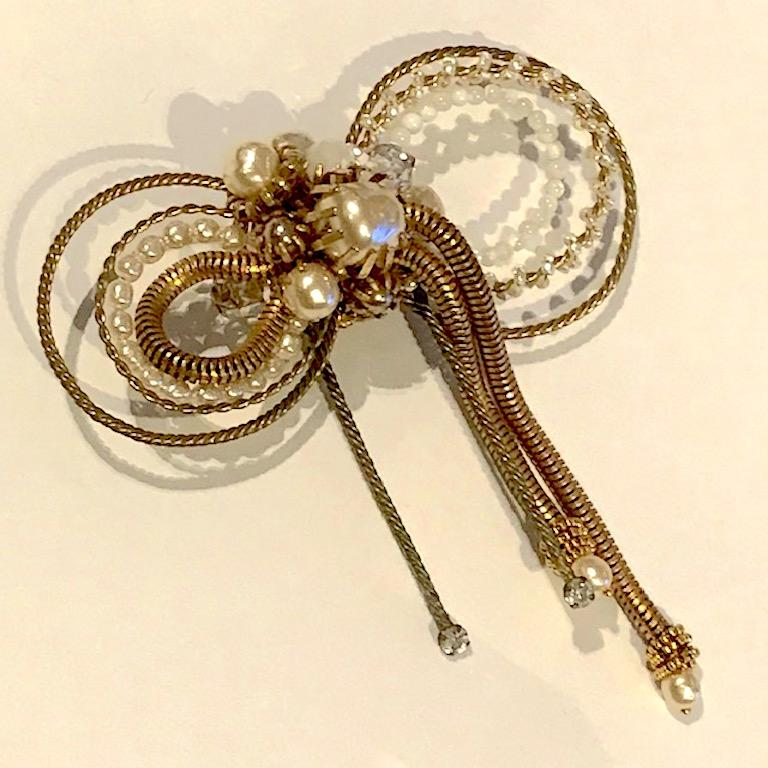 A beautiful, lovely and a very fine large bow brooch by Miriam Haskell. It has a soft antique gold tone patina know as Russian gold by the company. Faux small and large baroque pearls, medium size faux grey pearls, crystal and mother of pearl beads.