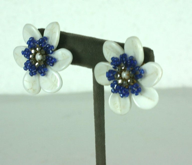 Charming Miriam Haskell Milk Glass Flower earrings with hand sewn seed bead detailing. Milk glass petals form the flower with a center of purpley blue seed beads with a crystal diamante center. Clip back fittings. 1950's USA. Excellent condition.