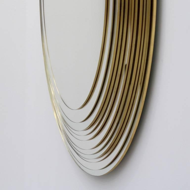 Eleven mirrors superimposed by the Designer Sam Baron, assisted by the glassmaker Yvon Goude, are homothetic declinations multiplying the essential perfect and infinite form of the oval / egg / face. In a subtle and intriguing way, the gold leaf is