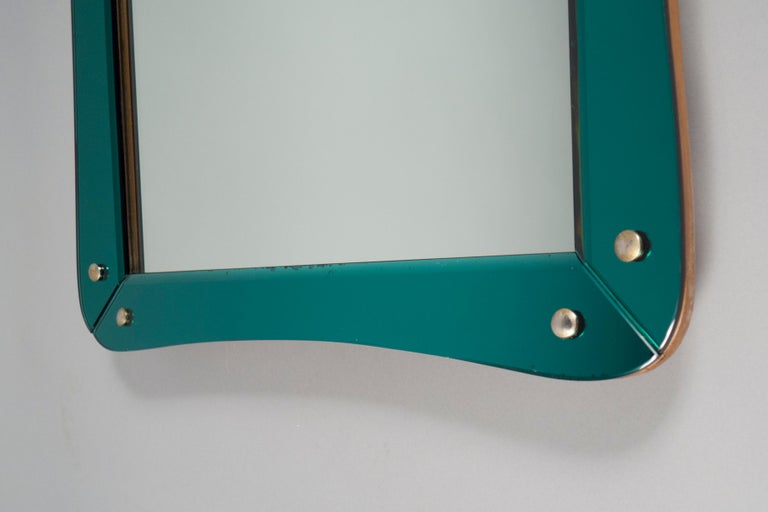 Rectangular wooden mirror, clad in deep turquoise mirrored glass panels, held by brass buttons.