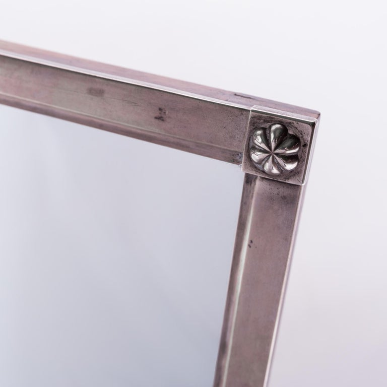 A mirror that is an early example of the Biedermeier style. Smooth silver frame with a beautiful gloss. Decorative elements in the form of rosettes placed on the corners of the frame. Signed at the top of the B.E frame, they were probably the