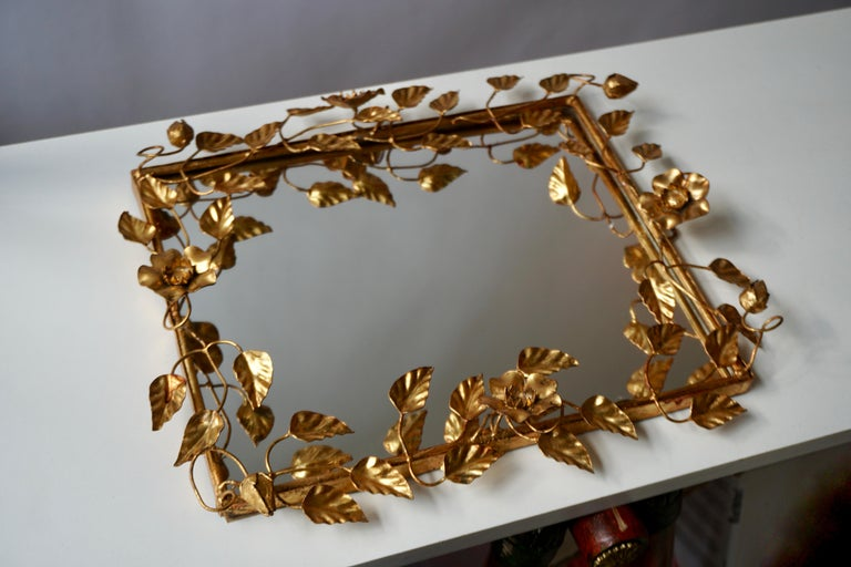 Italian mirror in gilded metal, 1960-1970s  The flowers and leaves are softly arranged on a wire structure with a harmonious design in order to create a lively and elegant whole.   Measures: Height 43 cm. Width 38 cm. Depth 6 cm.